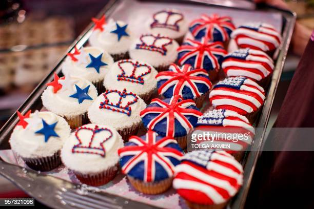 A member of staff at the Hummingbird Bakery poses with cupcakes themed with icing depicting the Union Flag the US flag stars and crowns to mark the...