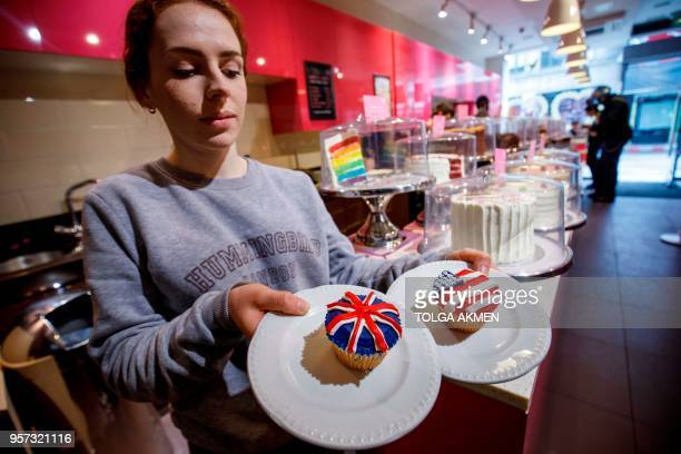 Member of staff at the Hummingbird Bakery poses with cupcakes themed with icing depicting the Union Flag and the US flag to mark the upcoming Royal...