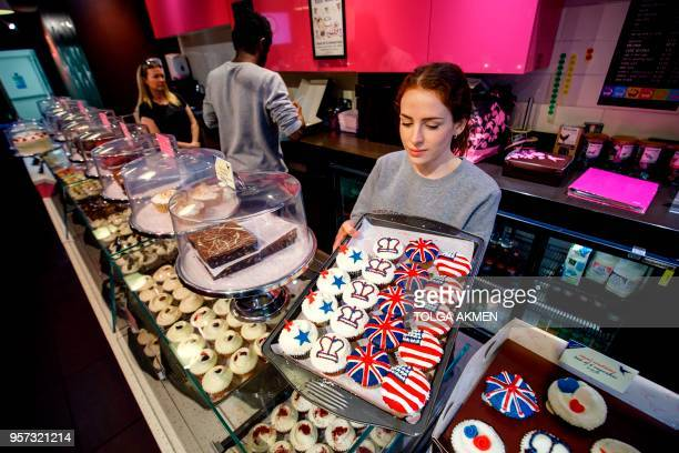 Member of staff at the Hummingbird Bakery poses with cupcakes themed with icing depicting the Union Flag, the US flag, stars and crowns to mark the...