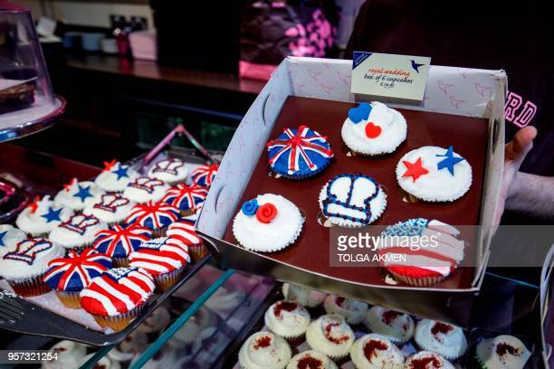 Member of staff at the Hummingbird Bakery poses with cupcakes themed with icing depicting the Union Flag, the US flag, stars, hearts and crowns to...