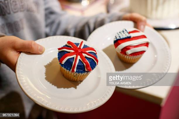 A member of staff at the Hummingbird Bakery poses with cupcakes themed with icing depicting the Union Flag and the US flag to mark the upcoming Royal...