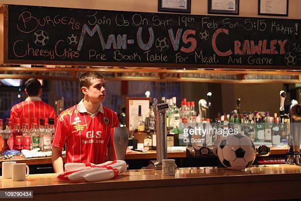 A member of staff at the Pelham Buckle pub watches as a coach carries fans of the nonleague football club Crawley Town to Manchester to watch their...