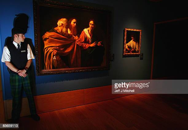 A member of staff at The Queen's Gallery at the Palace of Holyrood stands beside The Calling of Saints Peter and Andrew by Caravaggio on November 12...