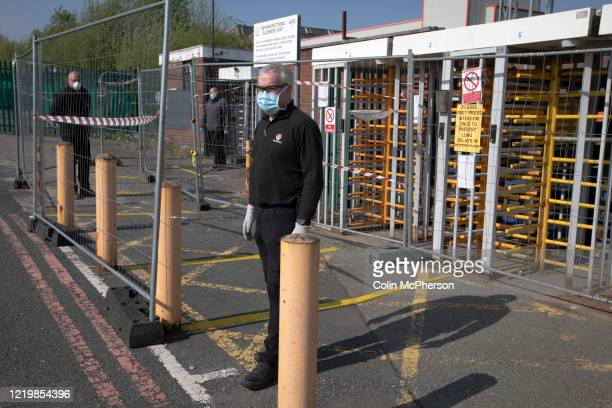 A member of staff at the redesigned workers' entrance at the Vauxhall car factory during preparedness tests and redesign ahead of reopening following...