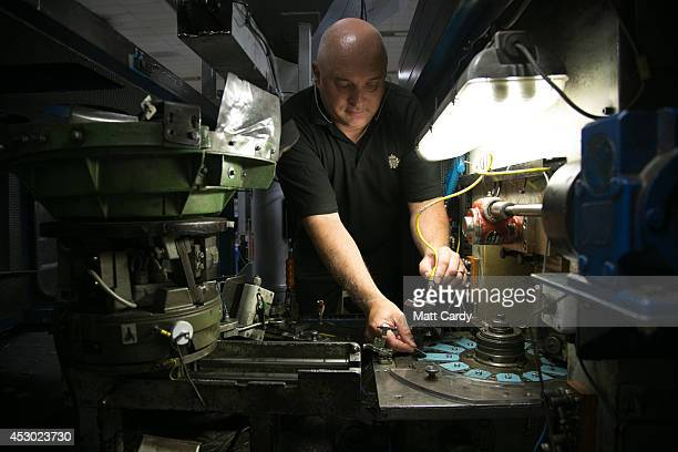 A member of staff at the Royal Mint produces new 50p coins on August 1 2014 in Llantrisant Wales The Royal Mint formed over 1100 years to produce...