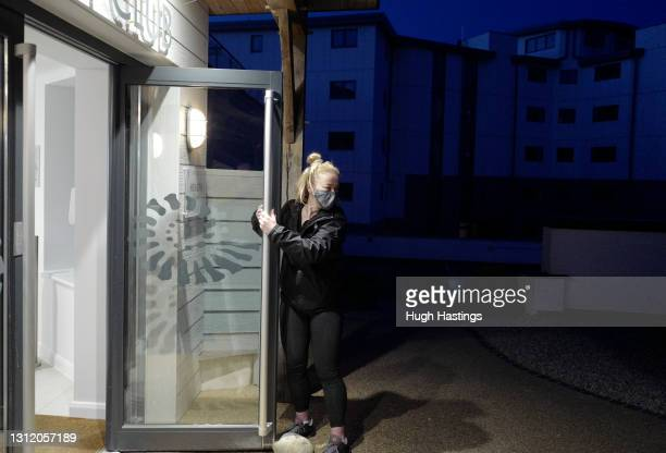 Member of staff at the St Michael's Health Club waits for customers to return at 6am on April 12, 2021 in Falmouth, England. England has taken a...