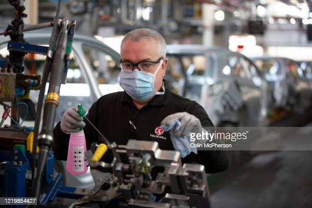 Member of staff at the Vauxhall car factory cleaning and disinfecting a work station during preparedness tests and redesign ahead of re-opening...