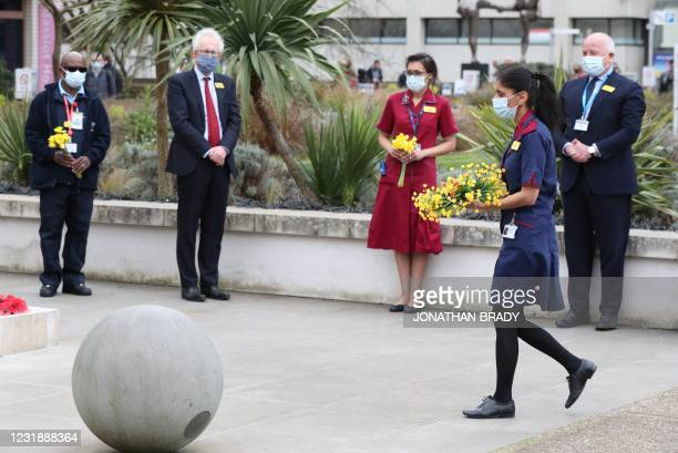 Member of staff carries flowers to place at the statue of Crimean War nurse Mary Seacole during a ceremony to observe a minute's silence on the first...