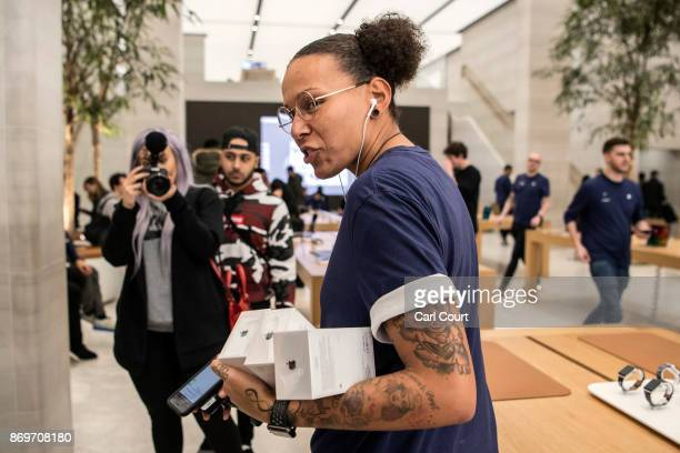 A member of staff carries iPhone X purchases to a customer upon their release in the Apple store on November 3 2017 in London England The iPhone X is...