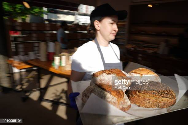 Member of staff carries loafs of bread at Gail's bakery-and-cafe in Salusbury Road, Queen's Park who are donating baked goods to NHS Workers on April...