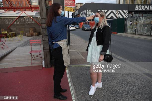Member of staff checks the temperature of theatregoers as a precaution against the transmission of the novel coronavirus upon their arrival ahead of...