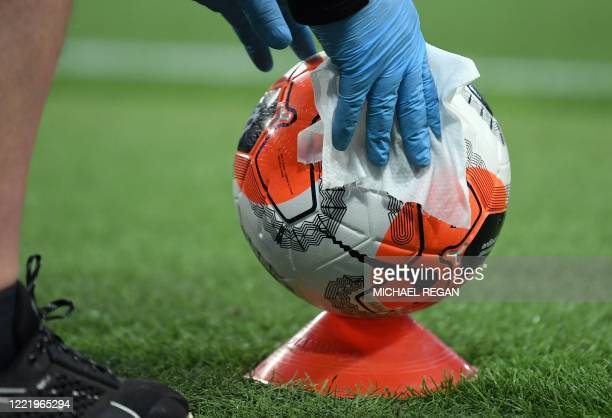 Member of staff cleans a ball during the English Premier League football match between Manchester City and Burnley at the Etihad Stadium in...