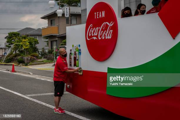 Member of staff cleans a sponsor vehicle before the Tokyo Olympic Games Torch Relay on June 26, 2021 in Hokuto, Japan. As the Olympic torch relay...