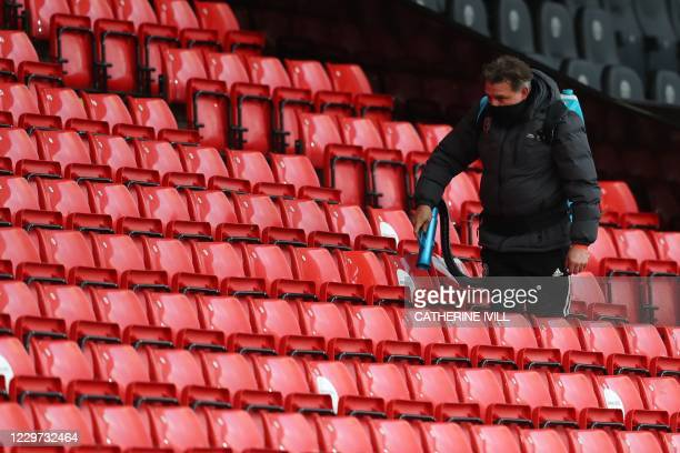 Member of staff cleans stadium seats where substitutes have been sitting during the English Premier League football match between Sheffield United...