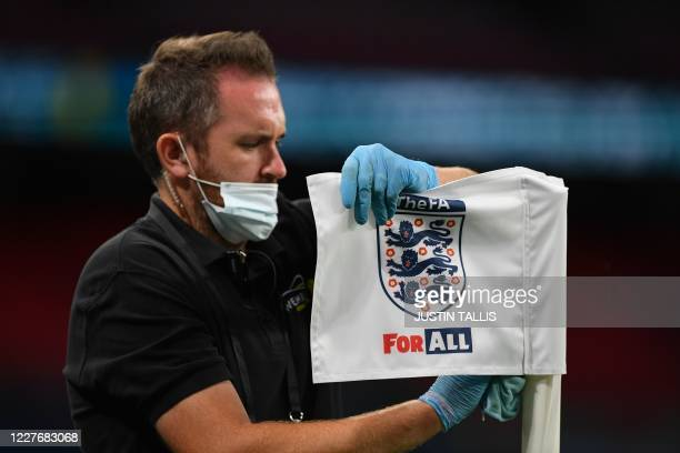 Member of staff cleans the corner flag during the English FA Cup semi-final football match between Arsenal and Manchester City at Wembley Stadium in...
