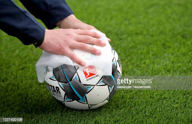 Member of staff cleans the match ball during half time during the Bundesliga match between RB Leipzig and Hertha BSC at Red Bull Arena on May 27,...