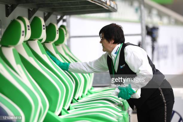 A member of staff cleans the substitute bench ahead of the Bundesliga match between VfL Wolfsburg and RB Leipzig at Volkswagen Arena on March 07 2020...