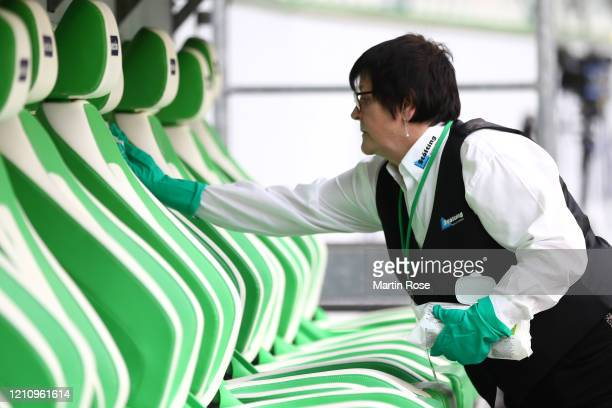 Member of staff cleans the substitute bench ahead of the Bundesliga match between VfL Wolfsburg and RB Leipzig at Volkswagen Arena on March 07, 2020...