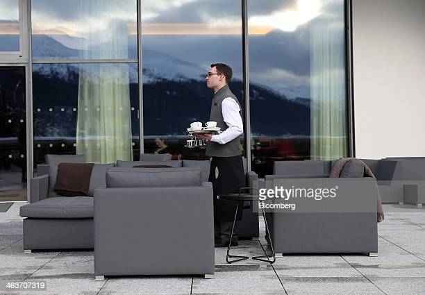 A member of staff clears away empty crockery from a table on the outside terrace at the InterContinental hotel Davos operated by InterContinental...