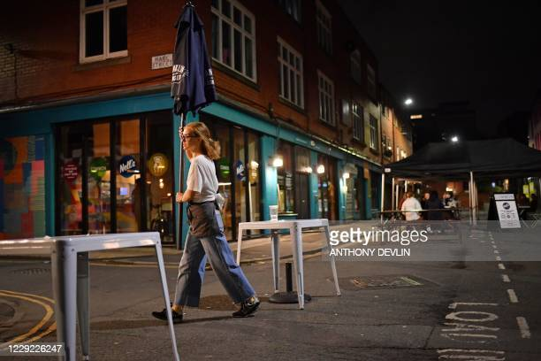 A member of staff clears away the furniture from an outside bar in Manchester city centre northwest England on October 22 2020 ahead of new...