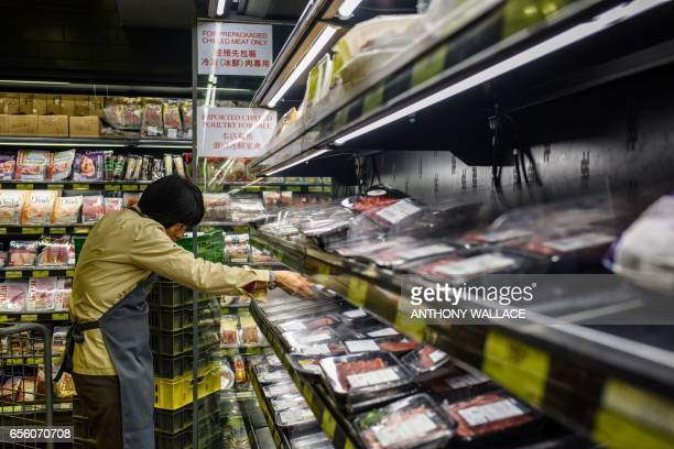 A member of staff clears packs of imported meat from Brazil off the shelves of a supermarket in Hong Kong on March 21 after Hong Kong's Centre for...