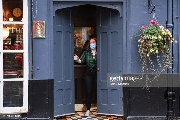 Member of staff closes a door of The Beehive pub in the Grassmarket following last orders at 6pm on October 9, 2020 in Edinburgh, Scotland. Pubs and...