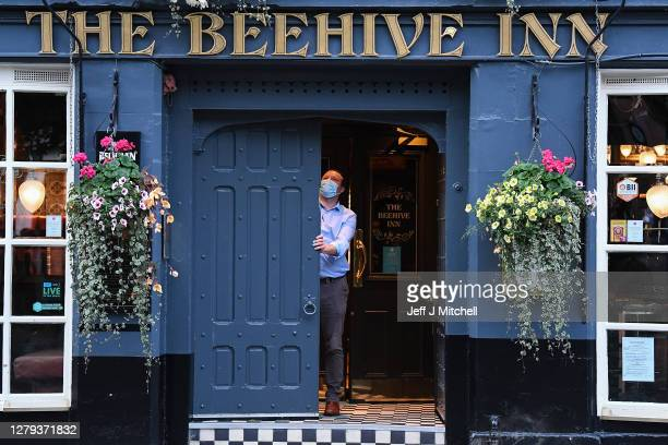 Member of staff closes the door of The Beehive pub in the Grassmarket following last orders at 6pm on October 9, 2020 in Edinburgh, Scotland. Pubs...