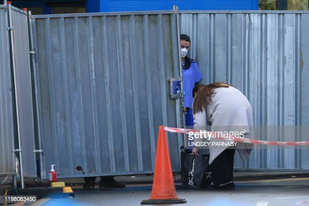 A member of staff comes to the entrance of the isolation accommodation at the Arrowe Park Hospital in Wirral near Liverpool in north west England on...