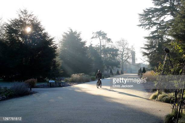 Member of staff cycles down the Broad Walk at The Royal Botanic Garden's Kew on January 22, 2021 in London, England. The Great Pagoda was completed...
