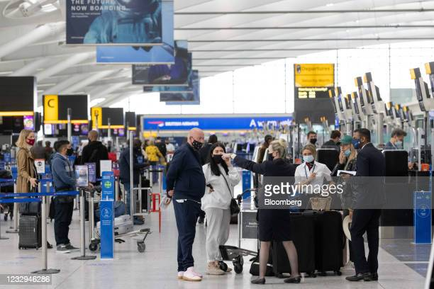 Member of staff directs passengers at check-in desks in Terminal 5 at London Heathrow Airport in London, U.K., on Monday, May 17, 2021. After a year...