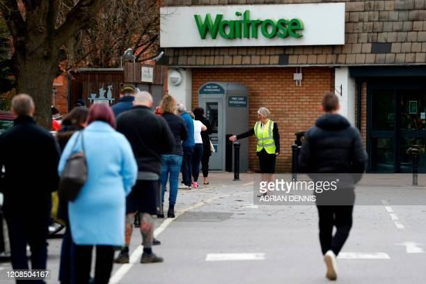 A member of staff enforces social distancing rules in a queue outside a Waitrose supermarket in Frimley south west of London on March 29 as life in...