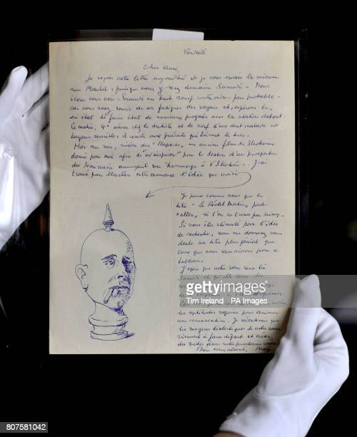 A member of staff examines one of the sketches on one of the letters in the collection written by surrealist Rene Magritte to poet Colinet which...