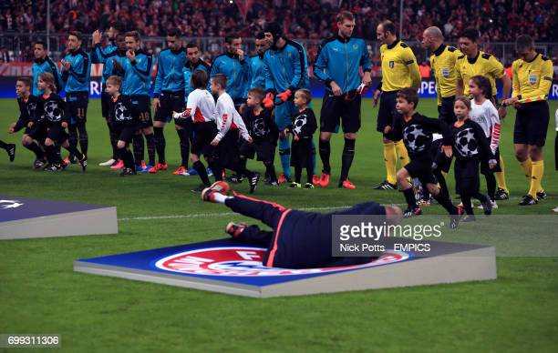 A member of staff falls over the Bayern Munich giant crest on the pitch before the game as the players line up for the anthems