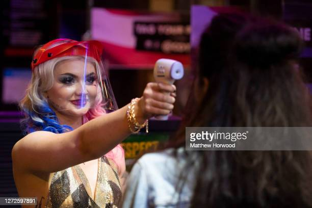 Member of staff from the Coyote Ugly bar wearing a face visor measures the temperature of a customer on entry on September 12, 2020 in Cardiff,...