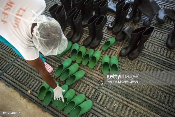 Member of staff from the Doctors Without Borders Drouillard Hospital in Cite Soleil, Haiti, arranges shoes for use in the Covid-19 patient care area...