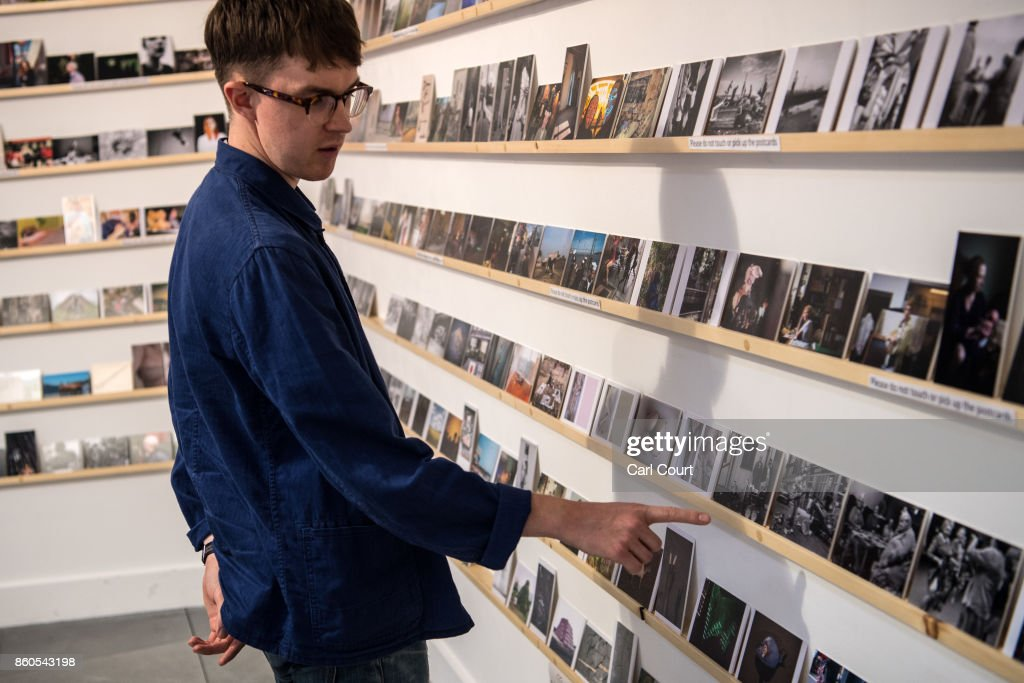 A member of staff gestures as he poses next to photograph postcards featuring images by photographers including Martin Parr and Wolfgang Tillmans ahead of a secret raffle at ThePrintSpace gallery on October 12, 2017 in London, England. The photographs will be on display from October 12- 24 and will be raffled on October 30 with all the money raised going to the Hepatitis C Trust's campaign to eliminate hepatitis C from the UK by the year 2030.