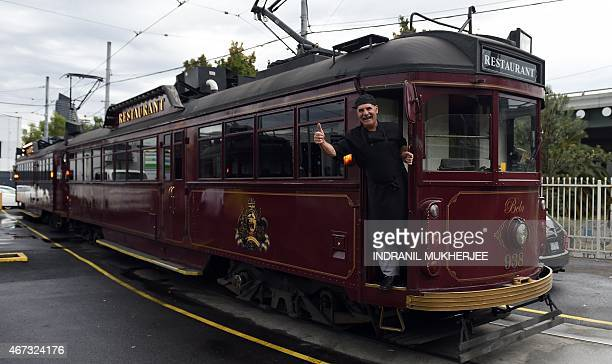 A member of staff gestures as one of the Colonial Tramcar Restaurant vintage trams prepares to pull out of the depot for the lunch service in...