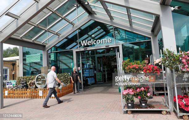 A member of staff greets a customer outside a Garden centre in Bagshot west of London on May 10 as life in Britain continues over the May Bank...