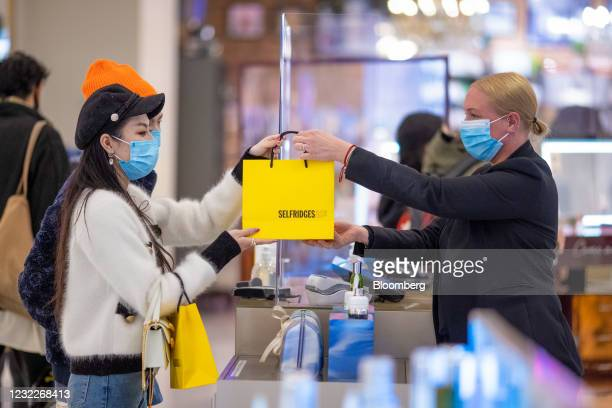 Member of staff hands a bag to a customer inside the Selfridges & Co Ltd. Department store in central London, U.K., on Monday, April 12, 2021....