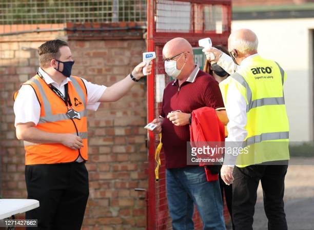 Member of staff has his temperature taken ahead of the EFL Trophy match between Cambridge United and Fulham U23 at Abbey Stadium on September 08,...