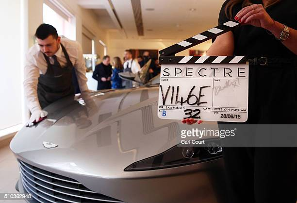 A member of staff holds a clapper board signed by Daniel Craig and used in the Bond film Spectre next to an Aston Martin DB10 used in the same film...