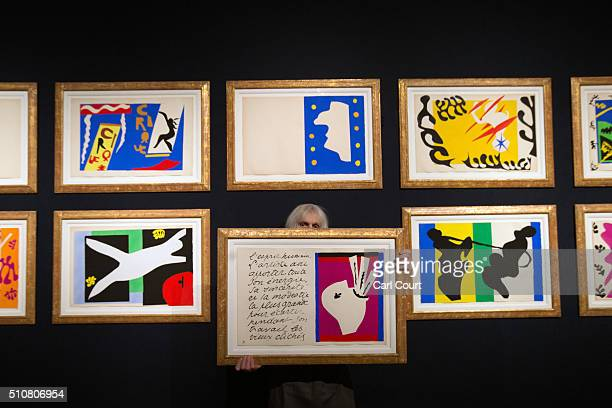 A member of staff holds a picture near a collection of Henri Matisse original prints from his jazz portfolio at Christie's auction house on February...
