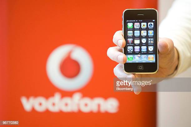 A member of staff holds an Apple iphone at a Vodafone store in London UK on Thursday Jan 14 2010 Vodafone Group Plc the world's biggest mobilephone...