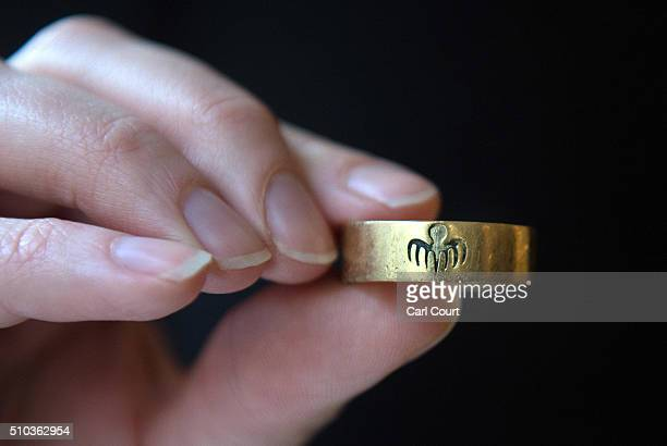 A member of staff holds Oberhauser's Spectre gold ring worn by Christoph Waltz in the Bond film Spectre during a photocall at Christie's auction...