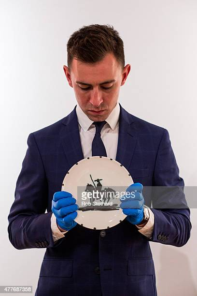 A member of staff holds 'Picador' a ceramic plate by Pablo Picasso estimated between £8001200 at Christie's King Street auction house on June 19 2015...