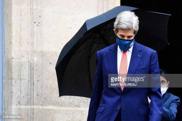 Member of staff holds the umbrella for US climate envoy John Kerry as he leaves the Hotel Roquelaure following his meeting French Ecological...