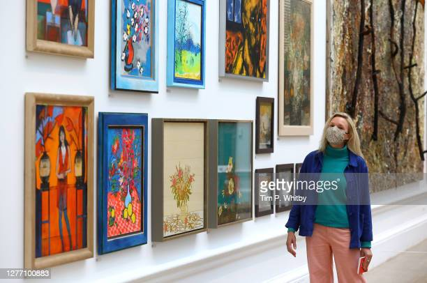 Member of staff inspects a selection of works during the press preview of the Summer Exhibition 2020 at The Royal Academy on September 28, 2020 in...