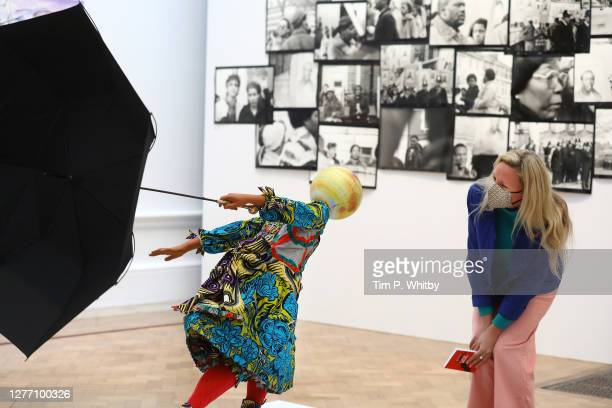 Member of staff inspects 'Air Kid by Yinka Shonibare RA during the press preview of the Summer Exhibition 2020 at The Royal Academy on September 28,...