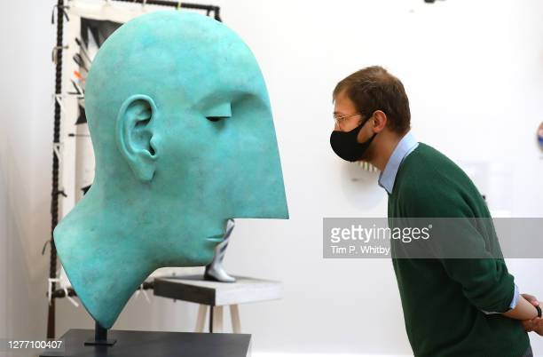 Member of staff inspects 'Head II' by Tim Shaw RA during the press preview of the Summer Exhibition 2020 at The Royal Academy on September 28, 2020...