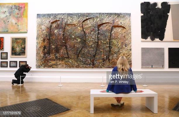 Member of staff inspects 'Vier Plus Eins' by Ian McKeever RA during the press preview of the Summer Exhibition 2020 at The Royal Academy on September...